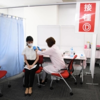 A Japan Airlines Co. employee receives a dose of the Moderna Inc. COVID-19 vaccine at a vaccination site set up at Haneda Airport in Tokyo on June 14. | BLOOMBERG