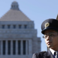 A Diet guard stands guards in front of the parliament building in Tokyo. | REUTERS