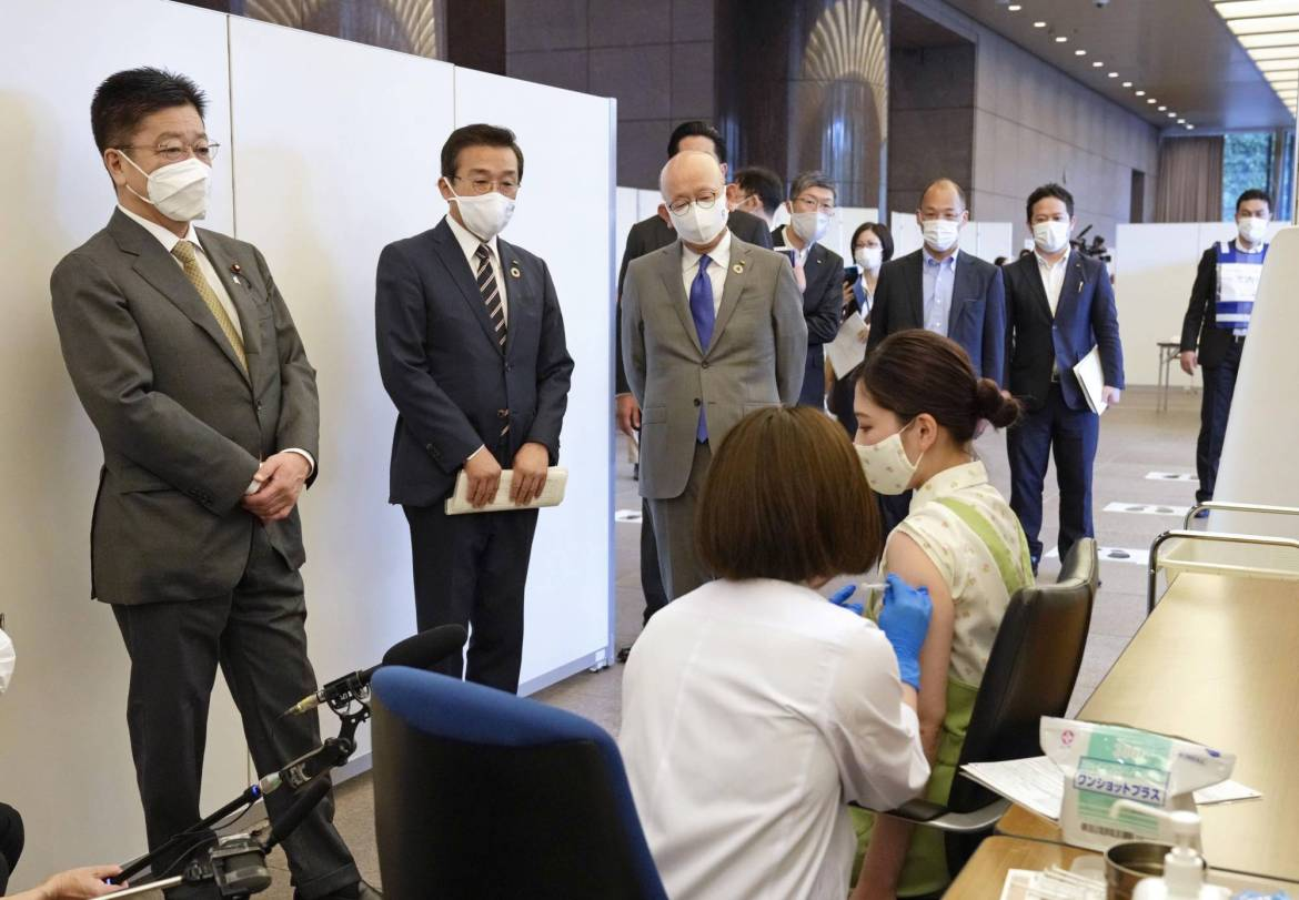 Chief Cabinet Secretary Katsunobu Kato (left) visits Itochu Corp. in Tokyo's Minato Ward on Monday at the start of the company's vaccination program for its workers. | KYODO