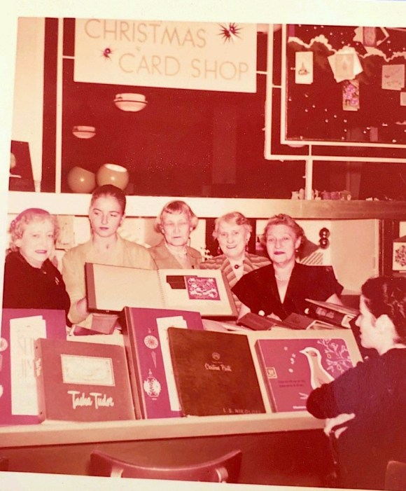 A group of Lord & Taylor Staff in 1956 gathered around that year's new Christmas Card Shop