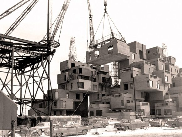 A crane lifting a prefabricated module for Habitat 67 into place.