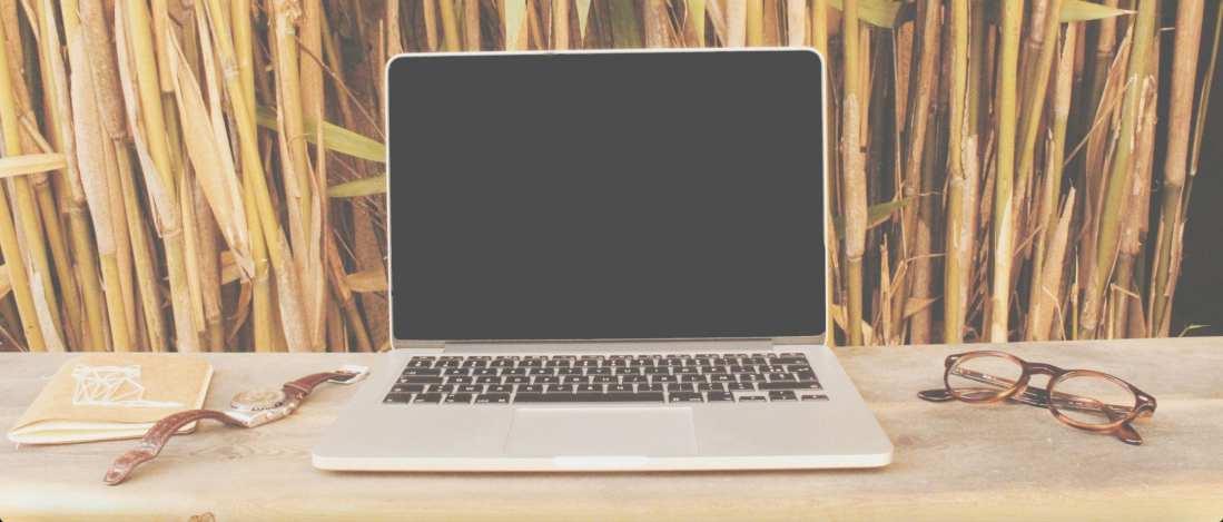 Mesa com um macbook e óculos ao lado.