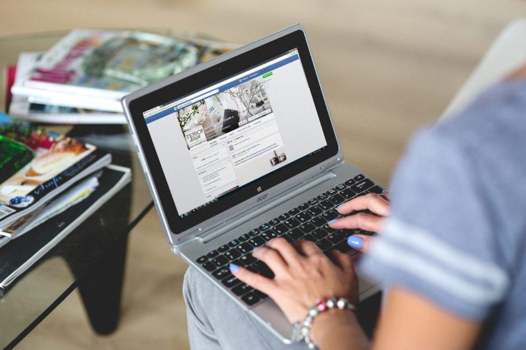 Mulher digitando no Facebook em laptop