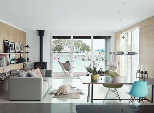 come_home_to_high_water-copehagen-floating-home-kitchen-dining-living-area-rais-stove-eames-chairs-glass-doors-alberto-meda-pendant-hay-sofa