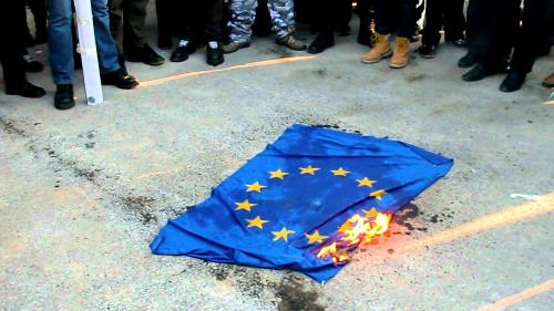 EU flag burning on the ground