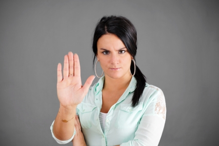 Dark haired woman making NO or STOP gesture with hand.
