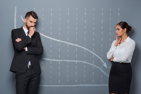 Two people before a graph warning of a recession.