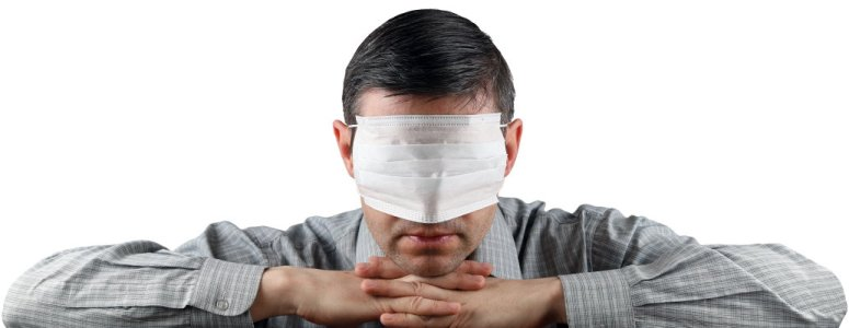 Man covers his eyes with a medical face mask.