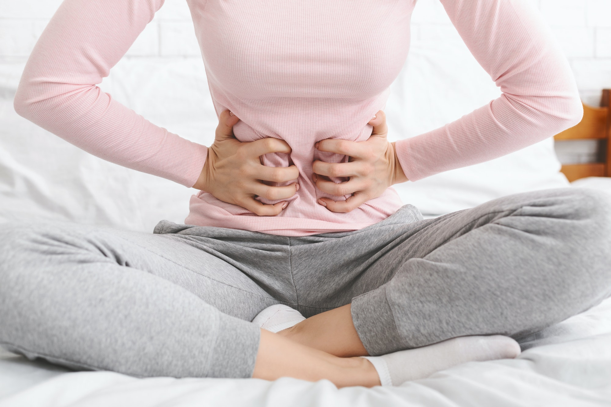Woman suffering from abdominal pain, sitting in bed