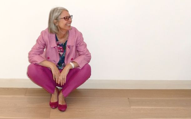 Kate Davies in pink jacket, trousers and shoes, sitting on the floor