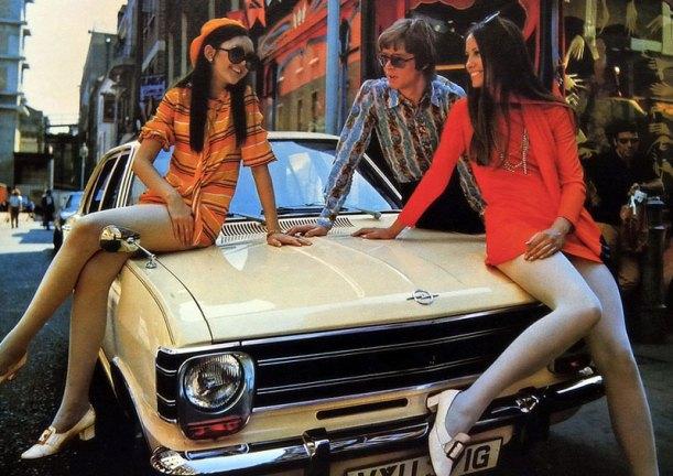 two women in mini skirts on a car bonnet