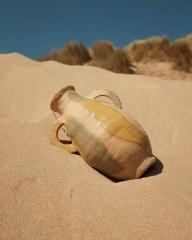 Ceramic pot sitting in the sand, by Victoria Ceramic