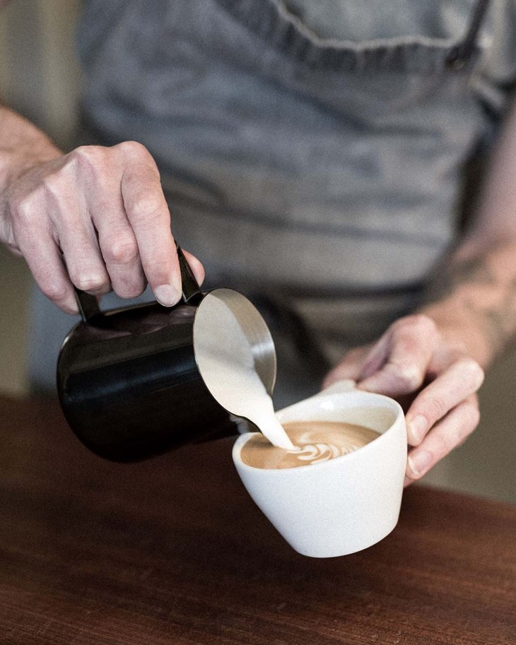 Close up of barista pouring frothy milk into a coffee cup and creating latte art