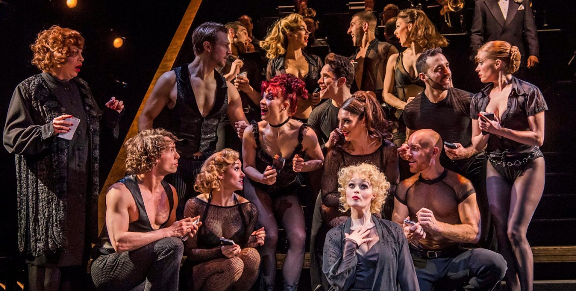 Sarah soetaert (roxie hart) centre seated with the cast of chicago, credit tristram kenton