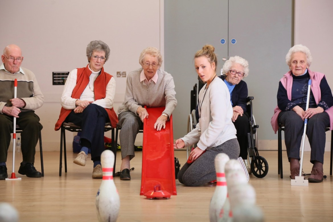 Female coach assisting older adults with red ramp 1400 (c) uk coaching