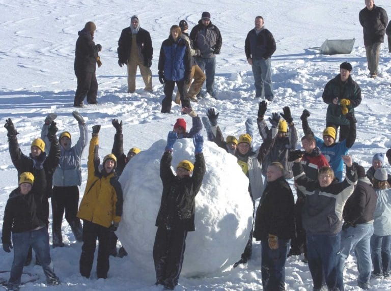 Group of people cheering next to massive snowball