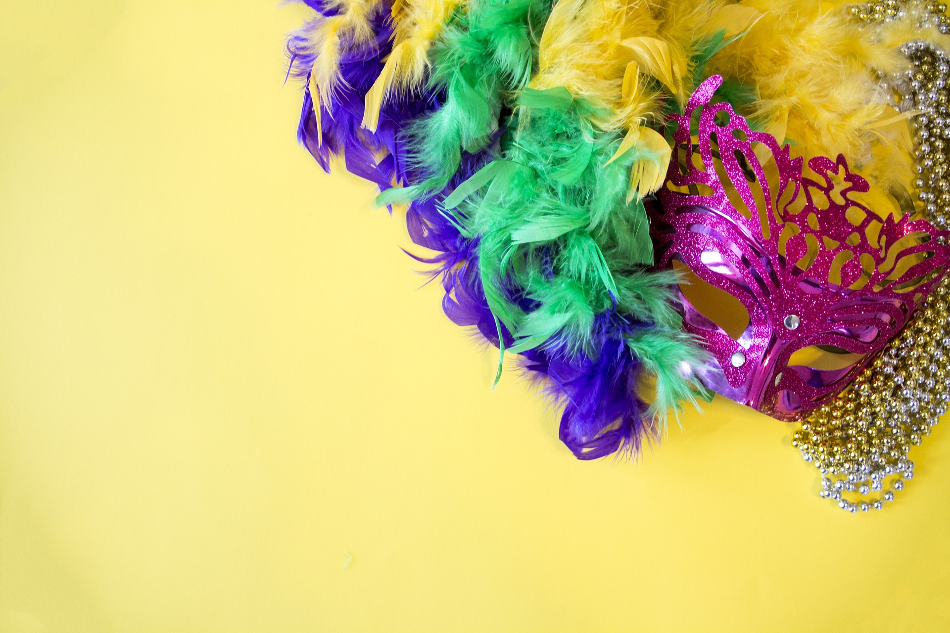 Colorful Mardi Gras mask with a boa on a yellow background