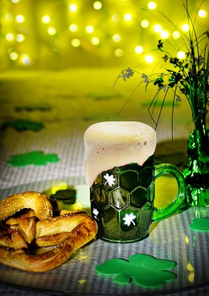 A pretzel and green beer with St. Patrick's Day decorations