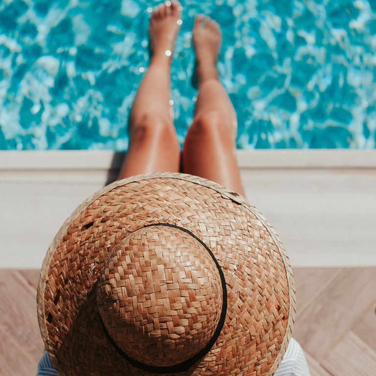 Girl in a hat with her legs in a pool