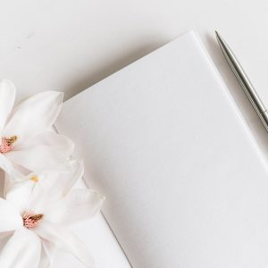 opened notebook and pen near flower