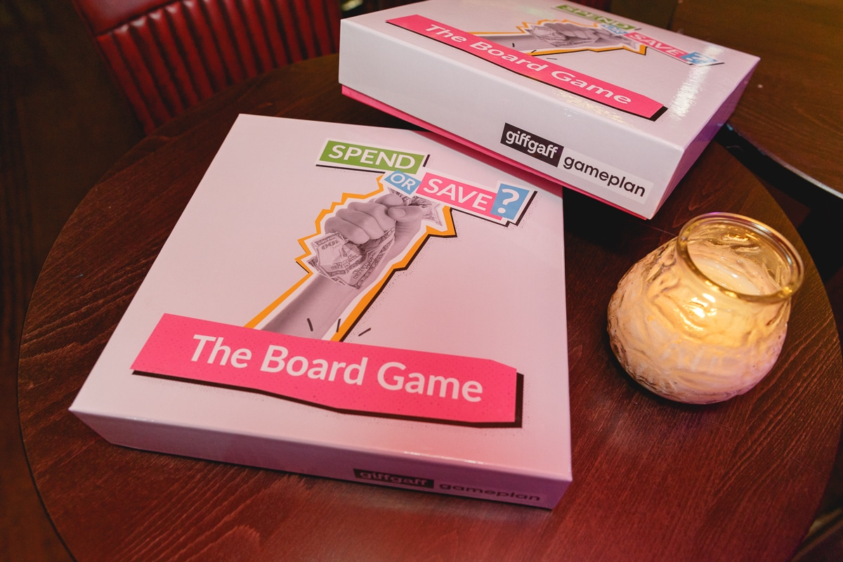 spend or save board game next to a candle