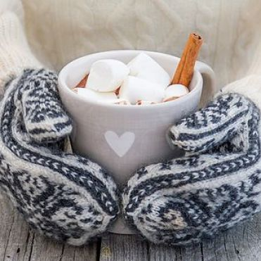 Hands in knitted mittens holding hot chocolate, rustic wood background