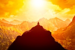 Woman meditating in sitting yoga position on the top of a mounta