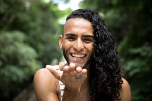 young genderqueer latino blowing a kiss and laughing