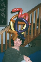 Photo of Barbara posing with a balloon hat on her head.
