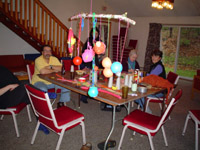 Photo of the group sitting around the table inside, with a work of their art hanging over the table