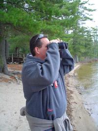 Photo of Ken outside looking through binoculars across the lake.