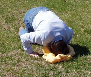 Photo of Pat outsdie kneeling in the grass his head down on a folded piece of clothing on the ground