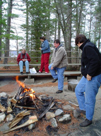 Photo of four members of the group standing or sitting close to the campfire.