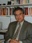 Photo of Raul E. Ybarra sitting at a desk with bookshelves behind him.