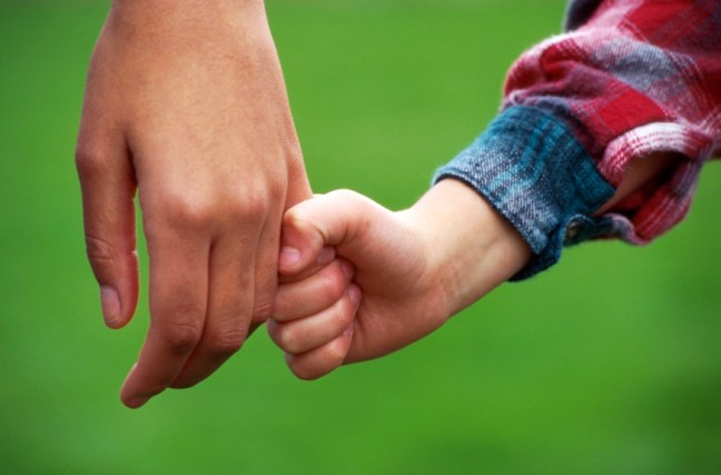 child holding hand of adult