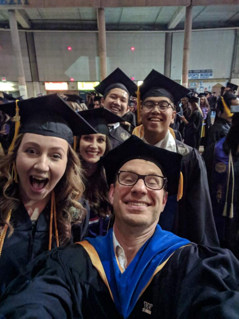 Students and professor in black robes and hats at graduation