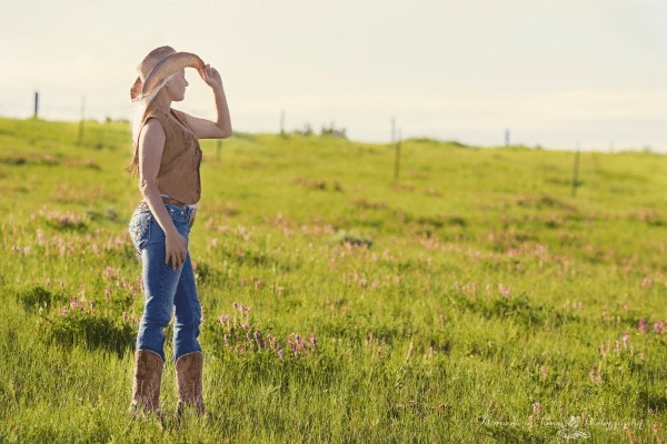 woman-with-cowboy-boots-and-hat-standing-in-grass-looking-away
