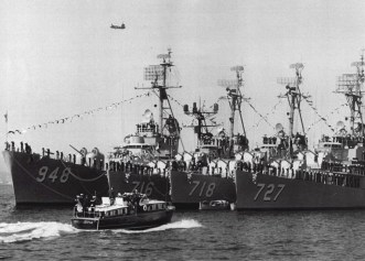 This photo was originally published in the November 1960 issue of CruDesPac News. The four ships were manning the rail to salute President Eisenhower as he passed by in his barge. The President is standing topside in the barge, midships. The other ships in the picture are USS Wiltsie (DD 716), USS Morton (DD948), and USS De Haven (DD727). Moored in San Diego Bay.