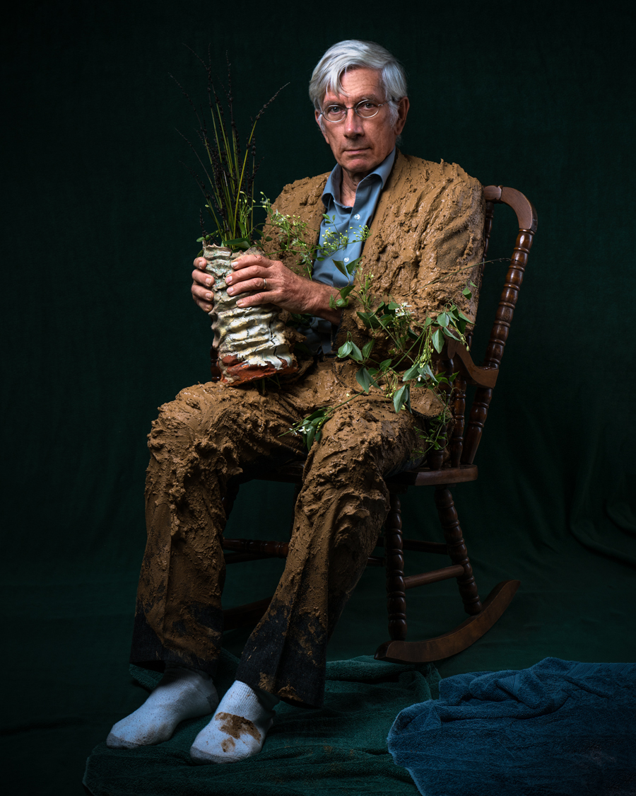 clay artist seated with vase and clay suit