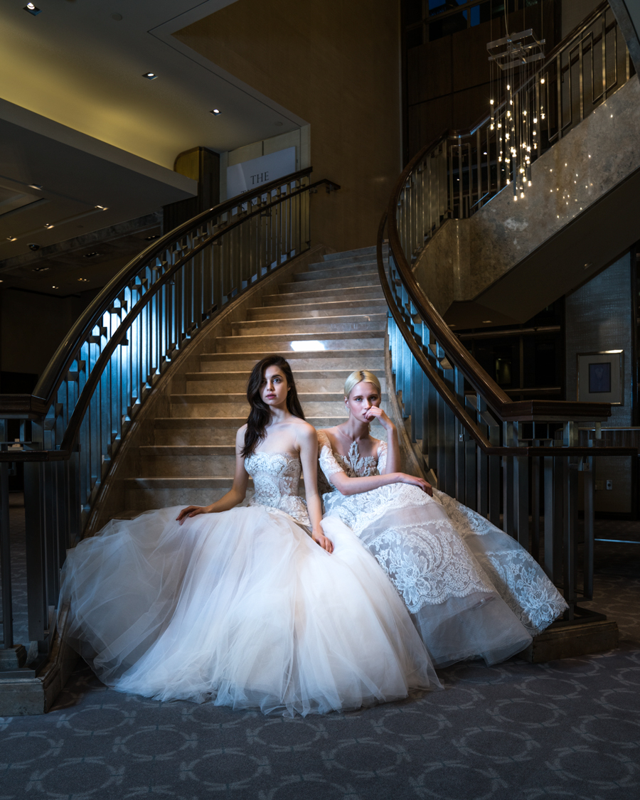 two models in bridal gowns seated on stairs