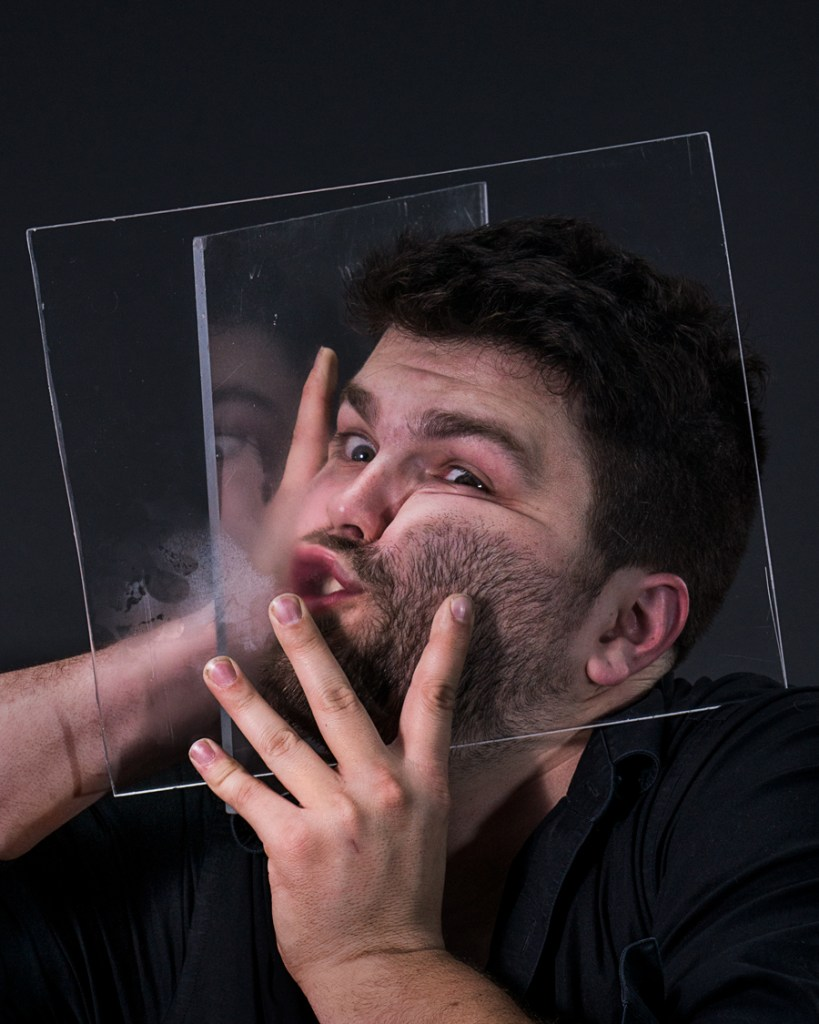 man squeezing head between two pieces of plexiglass