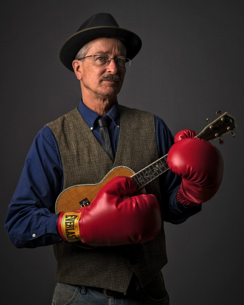 man with boxing gloves and ukulele