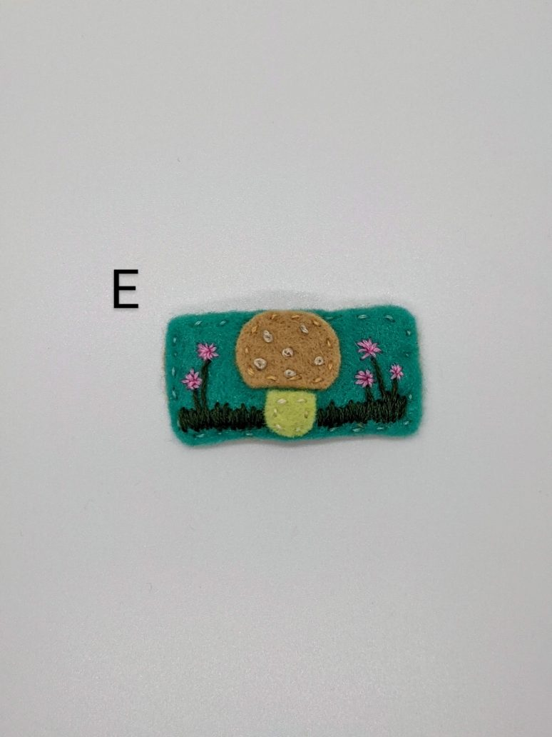 tan mushroom on green/teal background with embroidered flowers