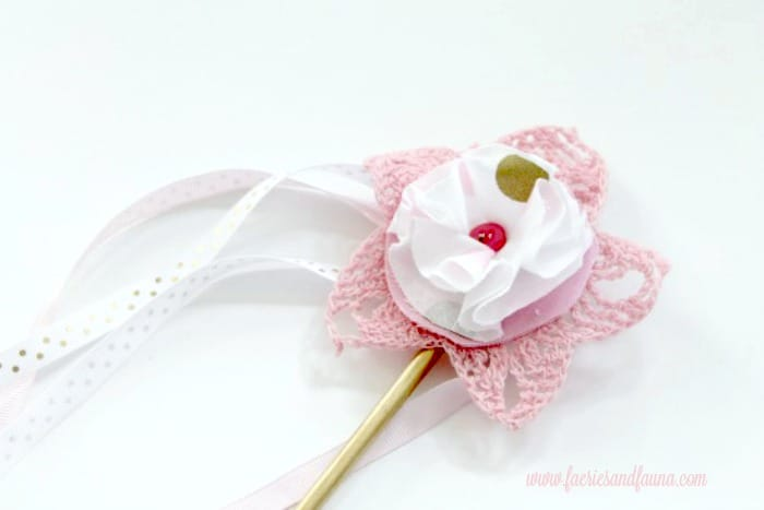 A free crochet toy pattern of a fairy wand in pink with polka dot flowers
