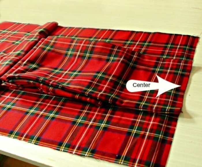 Pinning together a sash to a chair cover for sewing. A DIY Christmas chair cover.