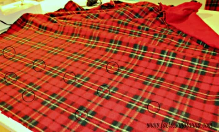 Making a thick warm red fleece Christmas throw blanket. This is a picture of a fleece blanket DIY being pinned together.