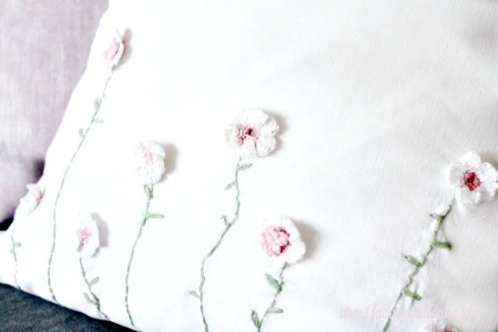 DIY Cushion Cover for Spring decor with little crocheted flowers and embroidered stems.  Throw pillow