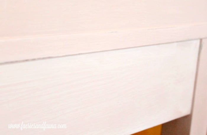 A white chalk paint layer giving a white wash effect to a refinishing furniture project.