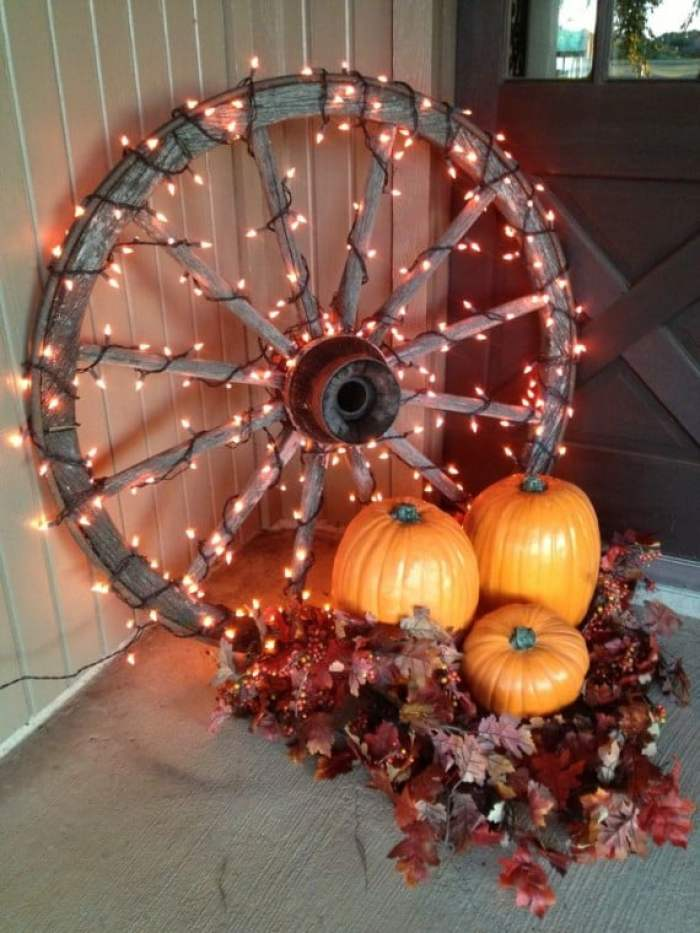 Outdoor fall decorations using lights. A rustic wagon wheel with pumpkins is a beautiful front porch fall decor idea.