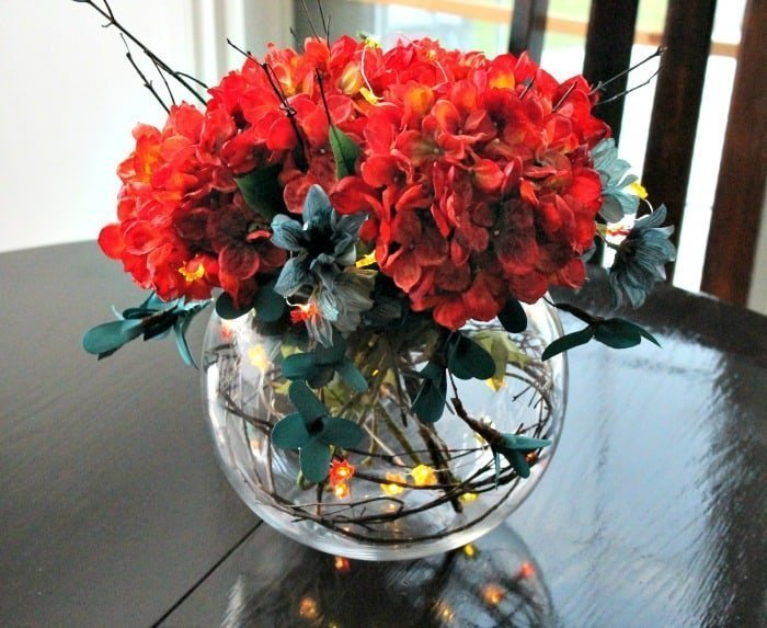 A fall floral arrangement using miniature lights. Pretty fall decoration centerpiece for a dining table or end table.